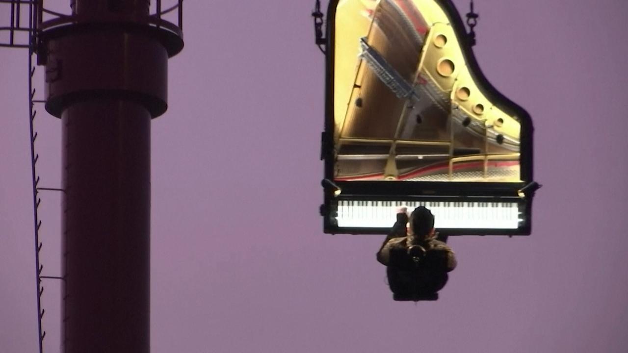 Pianist geeft concert bungelend aan hijskraan in München